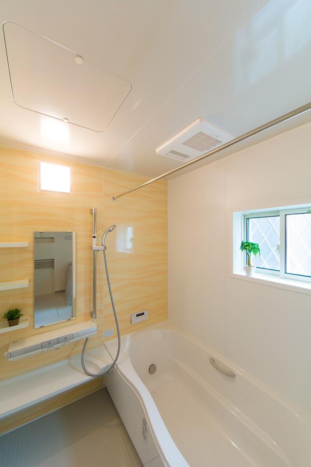 1階バスルーム。オレンジのアクセントパネルが温かみのある空間を演出。