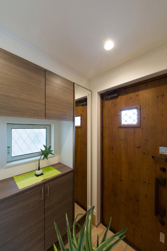 ナチュラルな雰囲気を演出するアイリッシュパインの玄関ドア。小窓部分から差し込む光が、明るく開放的ある空間を演出。