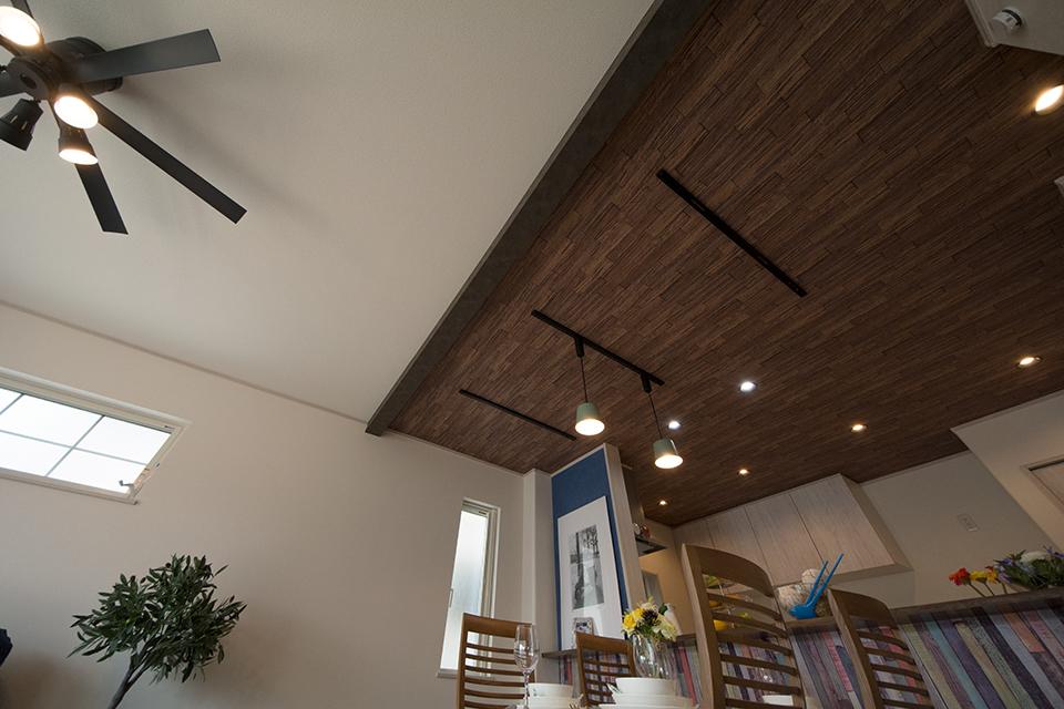 ウォルナットの木目調クロスをあしらい、ナチュラルな空間を演出するダイニング天井。