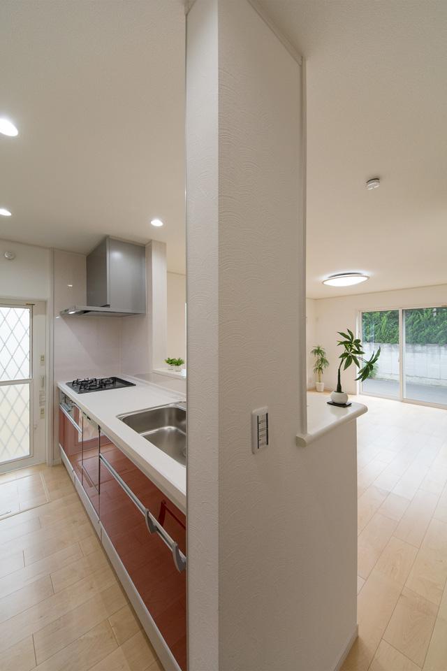 白を基調とした清潔感あるキッチン。赤のキッチン扉がエレガントな雰囲気を演出。