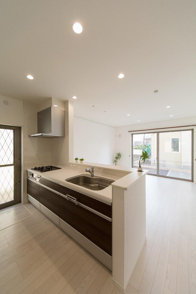 白を基調とした清潔感のあるキッチンスペース。オーク色のキッチン扉がナチュラルな雰囲気を演出。
