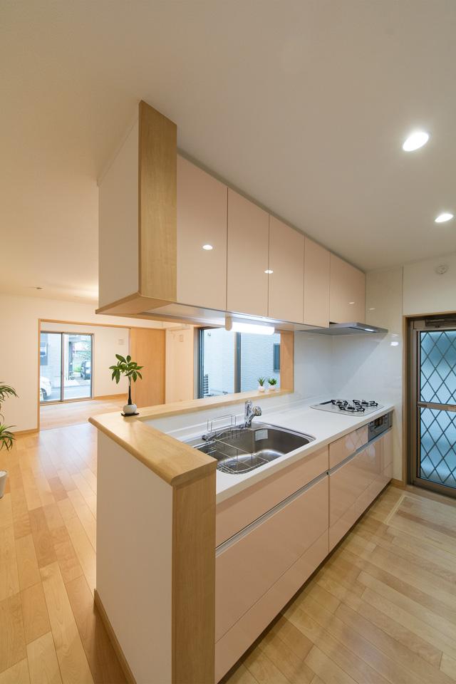 ミストピンクのキッチンパネルが明るく清潔感のあるキッチンスペースを演出します。