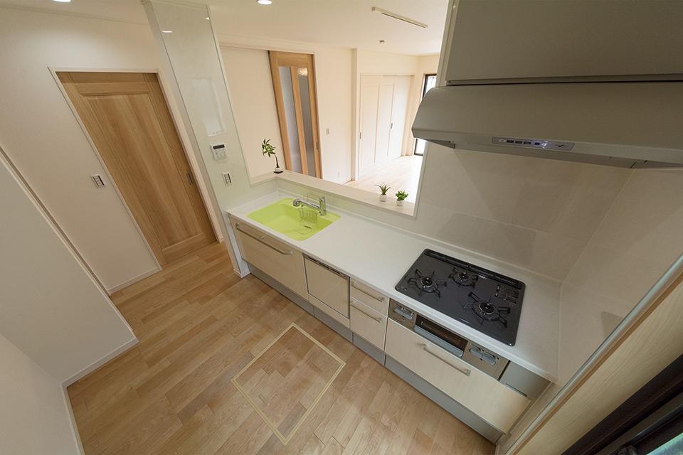 白を基調とした清潔感のあるキッチンスペース。ライムグリーンのシンクが印象的です。