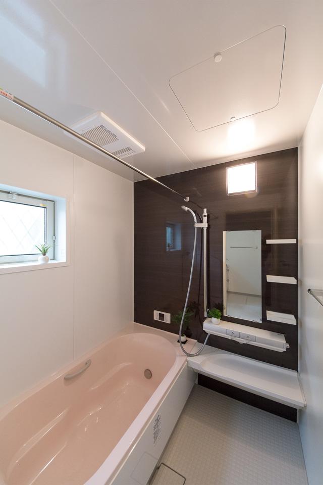 ライトピンクの浴槽が印象的なバスルーム。