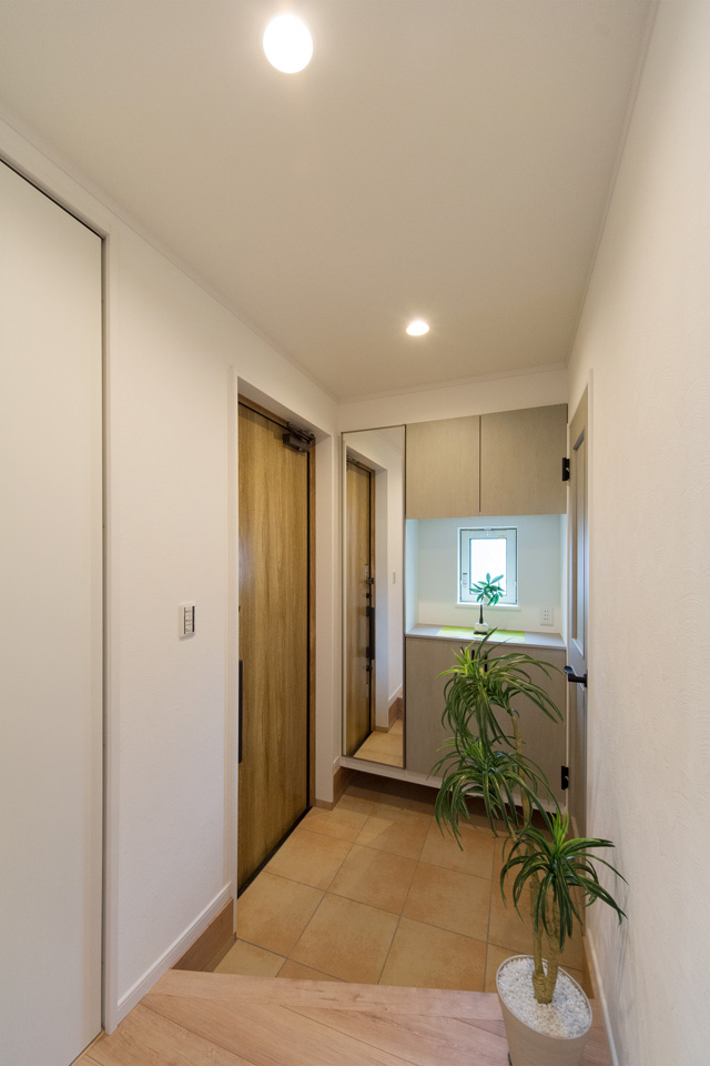 オーク調の玄関ドアとテラコッタ調タイルがナチュラルな雰囲気を演出する玄関。
