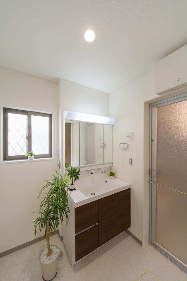 白を基調とした清潔感のあるサニタリールーム。ブラウンの洗面化粧台が印象的。