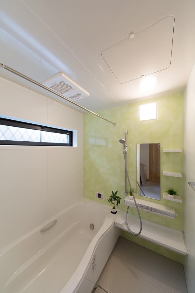 ミントグリーンのアクセントパネルが爽やかな印象のバスルーム。