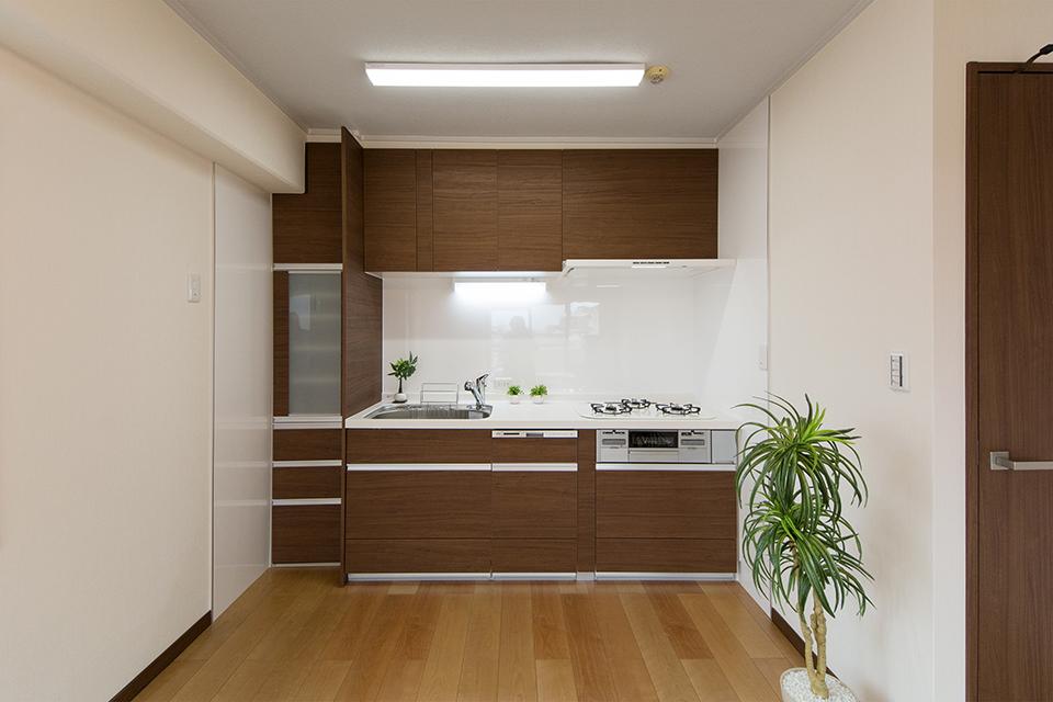 ウォルナット調のキッチン扉がナチュラルな印象を与えるシステムキッチン。パネルは清潔感のある白で仕上げました。