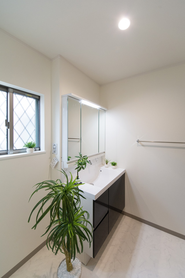 ブラウンの洗面化粧台がナチュラルな雰囲気の空間を演出するサニタリールーム。