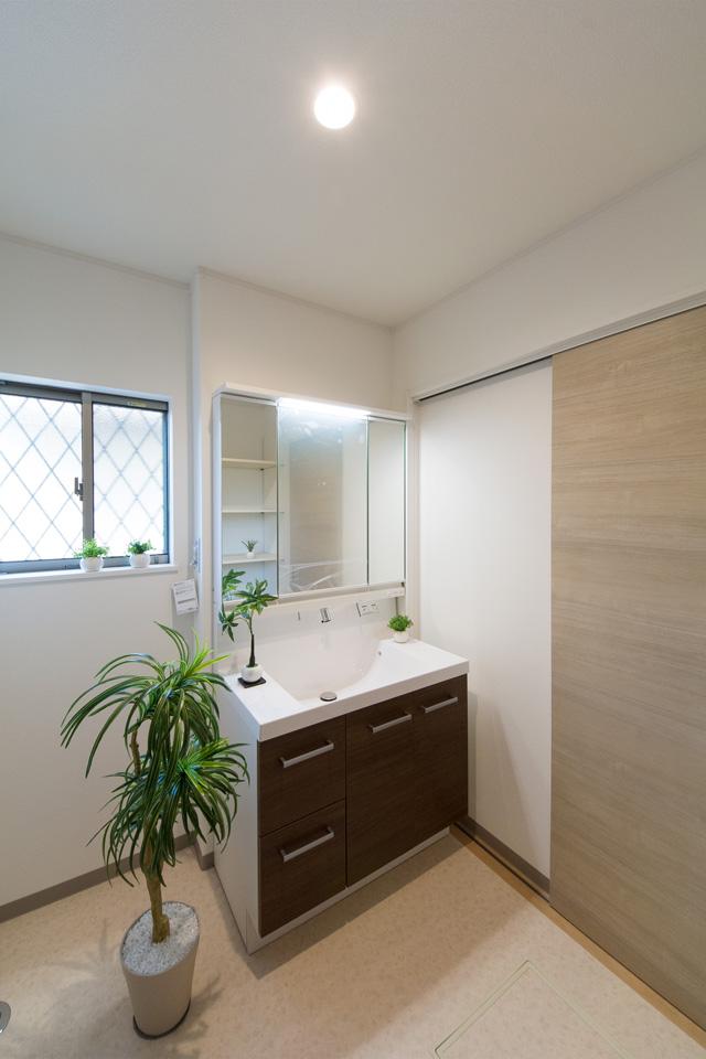白を基調とした清潔感のあるサニタリールーム。モカ色の洗面化粧台がナチュラルな雰囲気をプラス。
