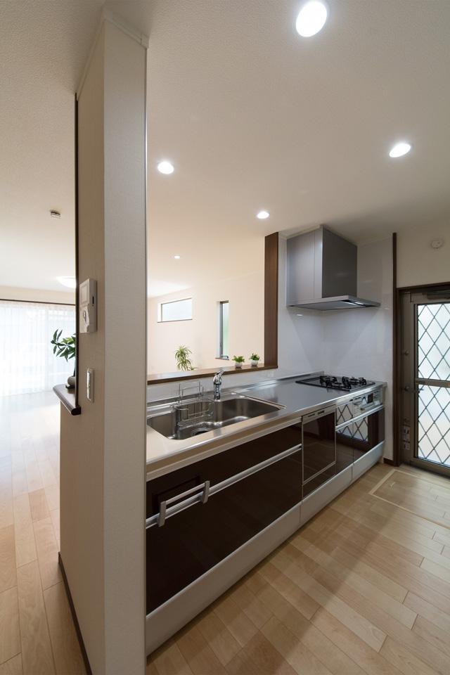 白を基調とした清潔感あるキッチン。ダークブラウンのキッチン扉がエレガントな雰囲気を演出。