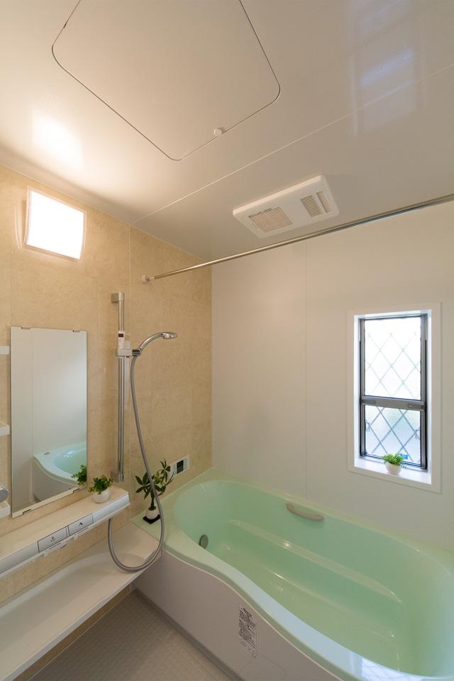 グリーンの浴槽が印象的なバスルーム。