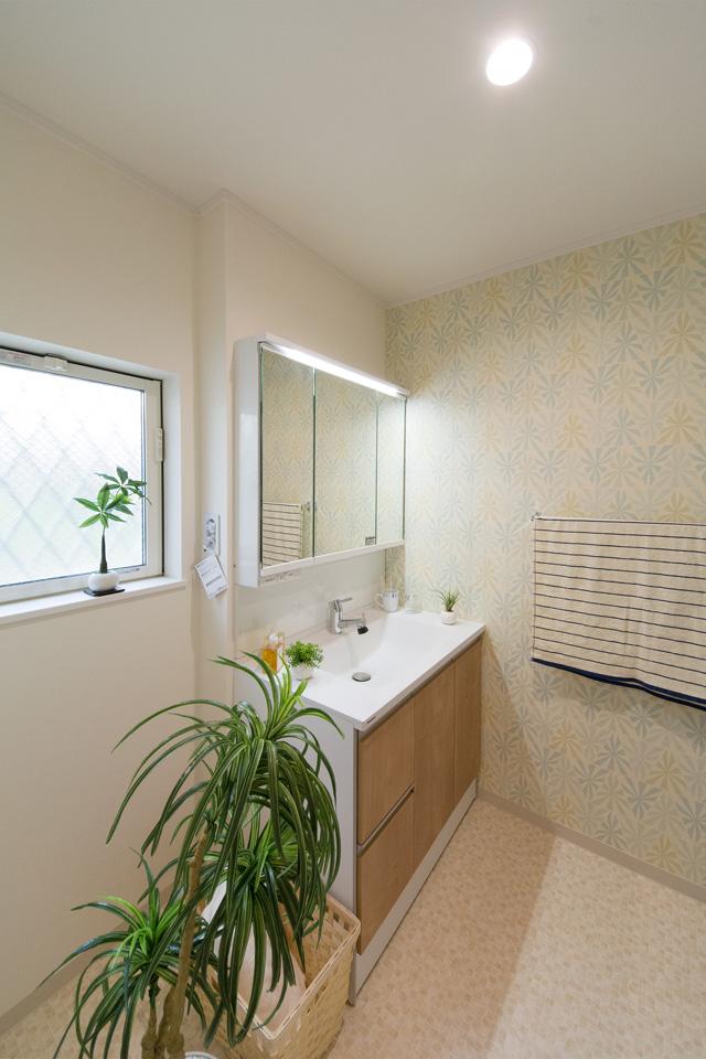 白を基調とした清潔感のある1階サニタリールーム。ブラウンの洗面化粧台がナチュラルな印象を与えます。