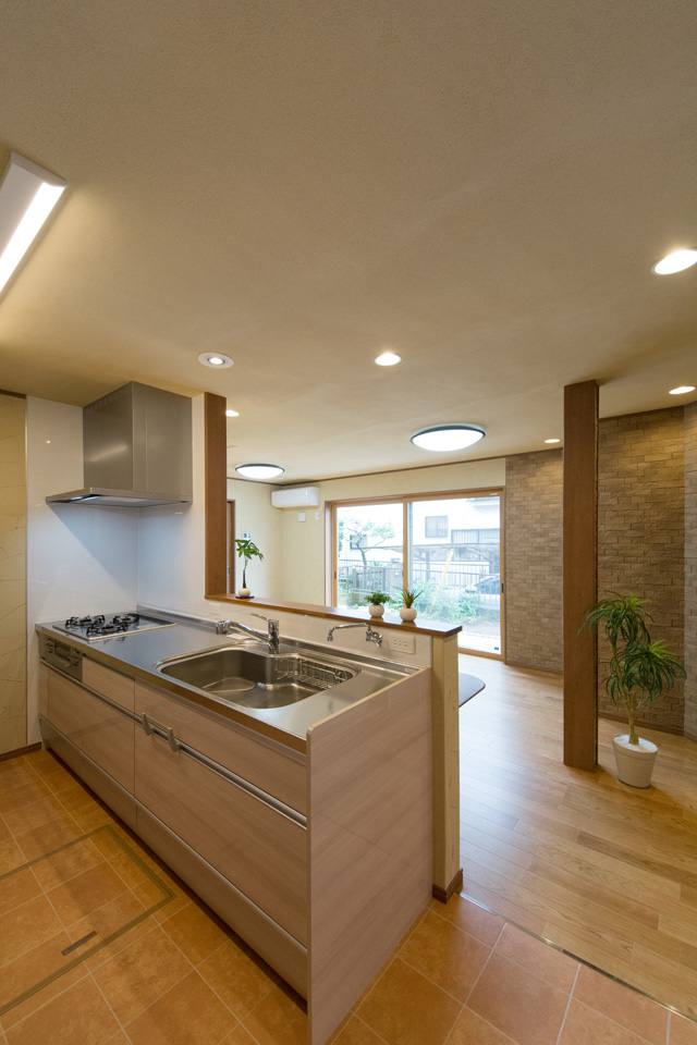 清潔感あるステンレストップのキッチン。ナチュラルな配色の扉がナチュラルな印象を演出。