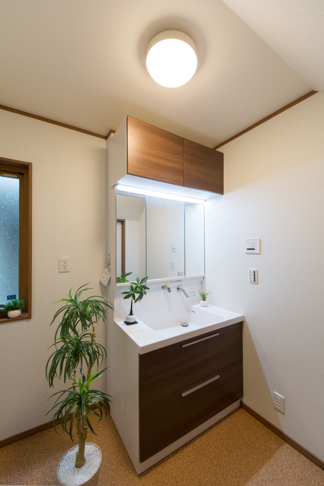 収納も豊富な洗面化粧台。ブラウンの扉がナチュラルな印象を演出。