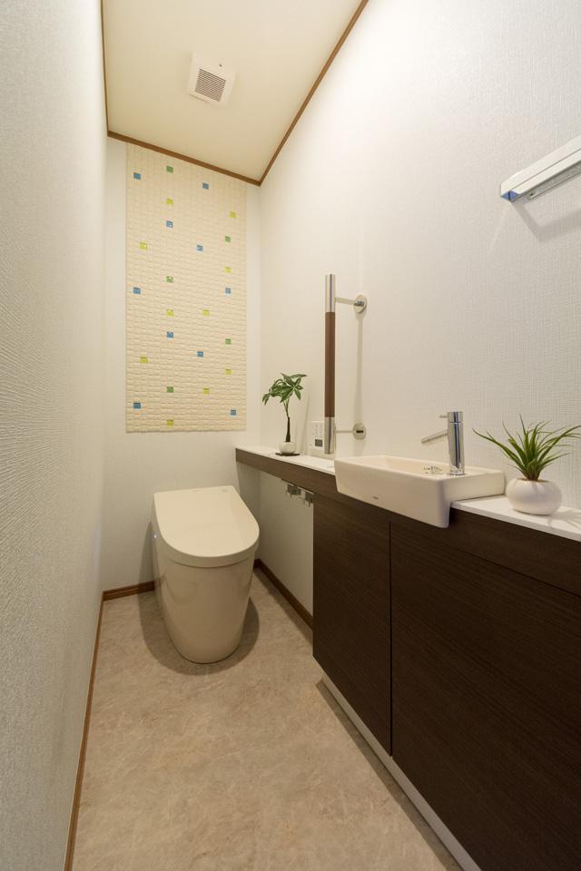 1階トイレ-見た目もすっきりとしたタンクレストイレを使用。壁にはエコカラットをあしらいました。