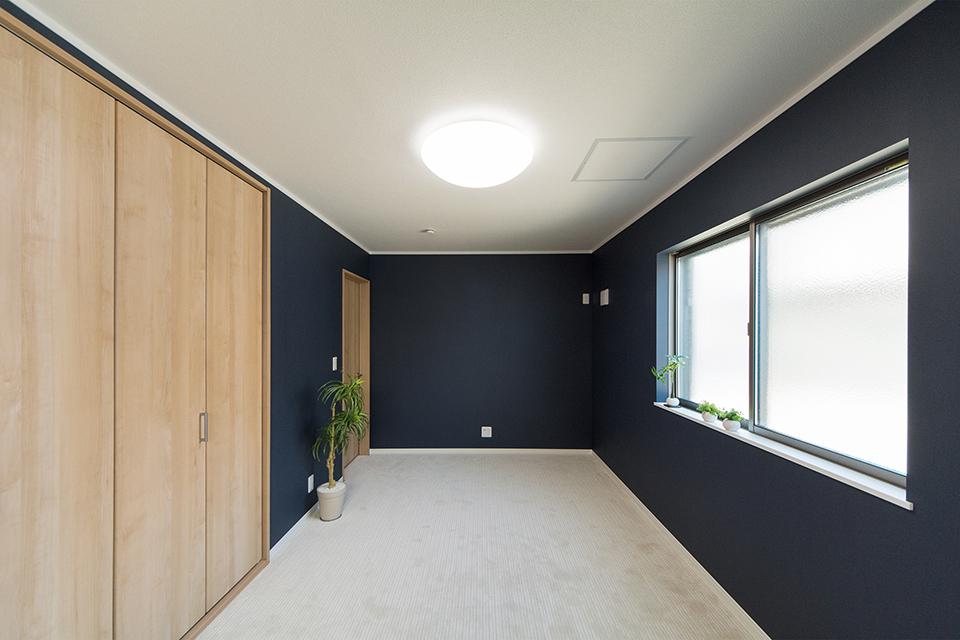 ネイビーのアクセントクロスで、シックな雰囲気に仕上げた1階主寝室。
