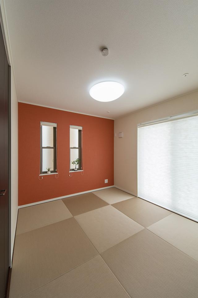 モダンな空間を演出する半畳市松敷き。朱色のアクセントクロスが印象的。