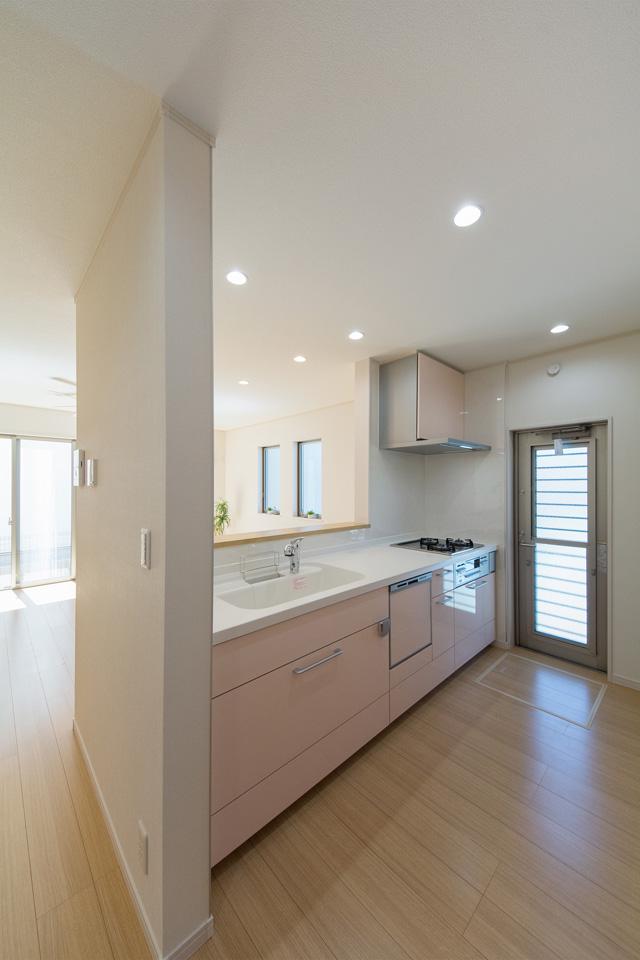 白を基調とした清潔感のあるキッチンスペース。ミストピンクのキッチン扉が爽やかな印象をプラス。