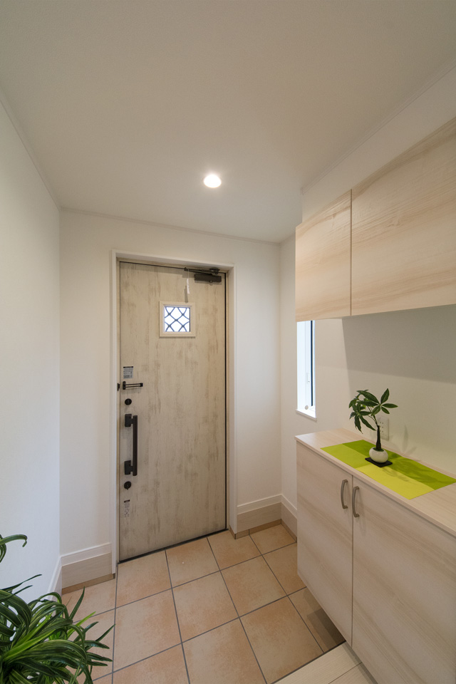 ナチュラルな雰囲気を演出するエクリュアイボリーの玄関ドア。窓部分から差し込む光が、明るく開放的ある空間を演出。