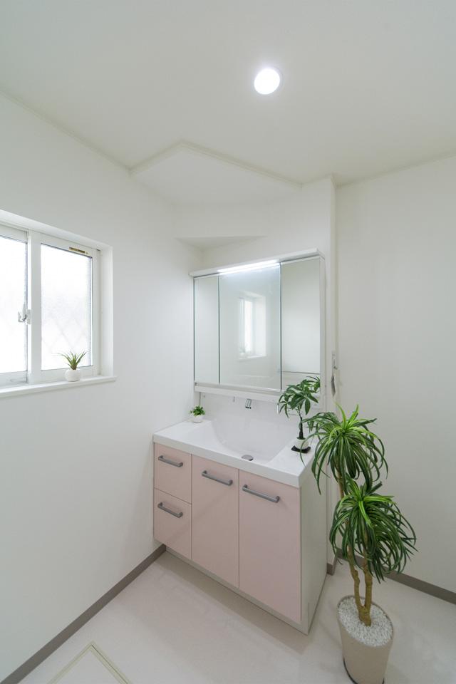 白を基調とした清潔感のあるサニタリールーム。パステルピンクの洗面化粧台が爽やかな印象を与えます。