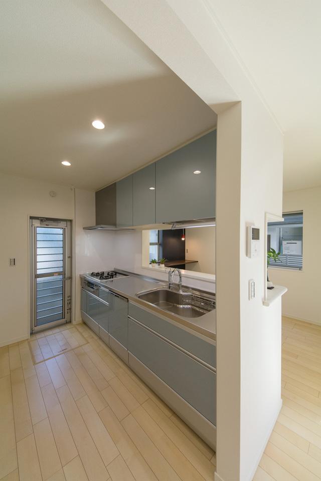 ブルーグレーのキッチン扉が爽やかな印象を与えるキッチンスペース。