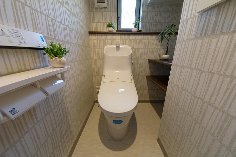 白を基調とした清潔感のある1階トイレ。ライトグレーのアクセントクロスが印象的。