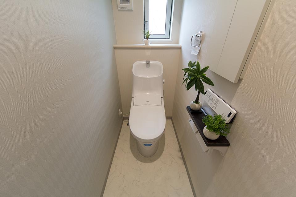 白を基調とした清潔感のある1階トイレ。アクセントクロスが落ち着いた雰囲気を演出。