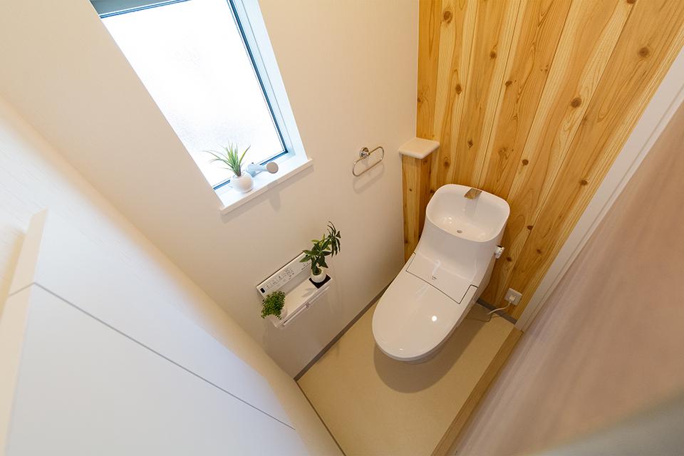 白を基調とした清潔感のある2階トイレ。ウッディ柄アクセントクロスがナチュラルな空間を演出。