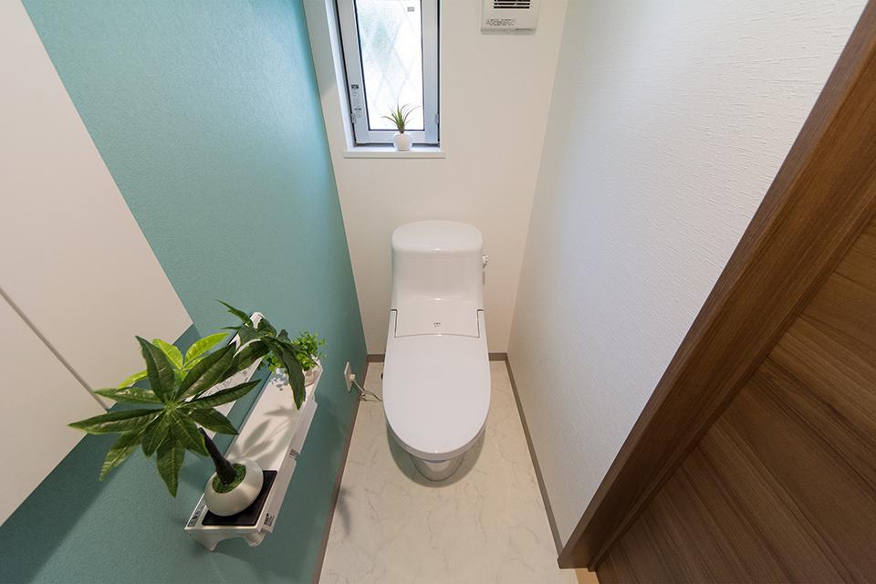 ターコイズブルーのアクセントクロスが爽やかな印象を与える1階トイレ。