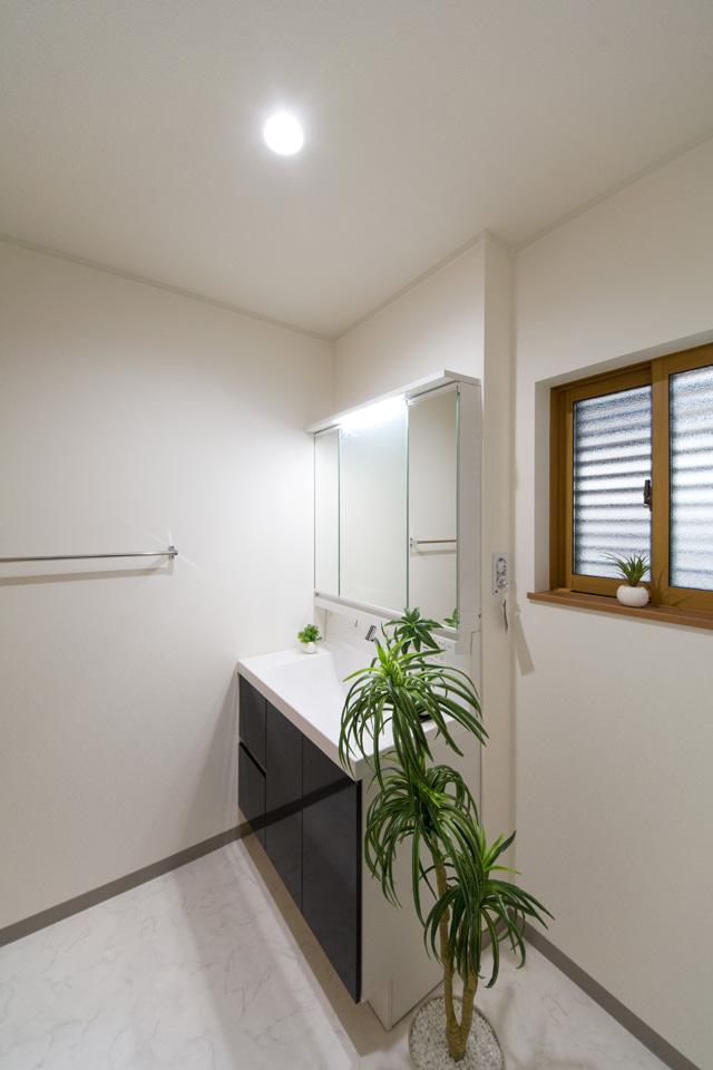 ディープグレーの洗面化粧台がナチュラルな雰囲気の空間を演出するサニタリールーム。