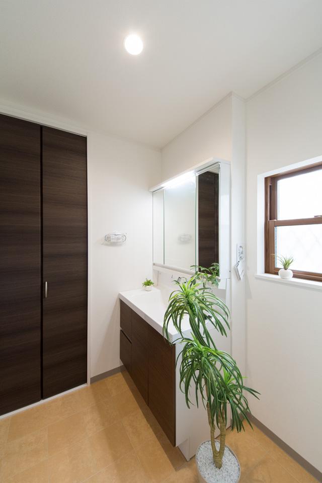 白を基調とした清潔感のあるサニタリールーム。ブラウンの洗面化粧台とテラコッタ調のフロアがナチュラルな雰囲気を演出。