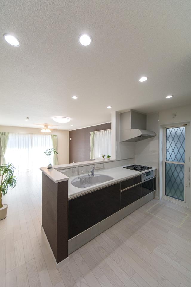 白を基調とした清潔感あるキッチン。ダーク色のキッチン扉がエレガントな雰囲気を演出。