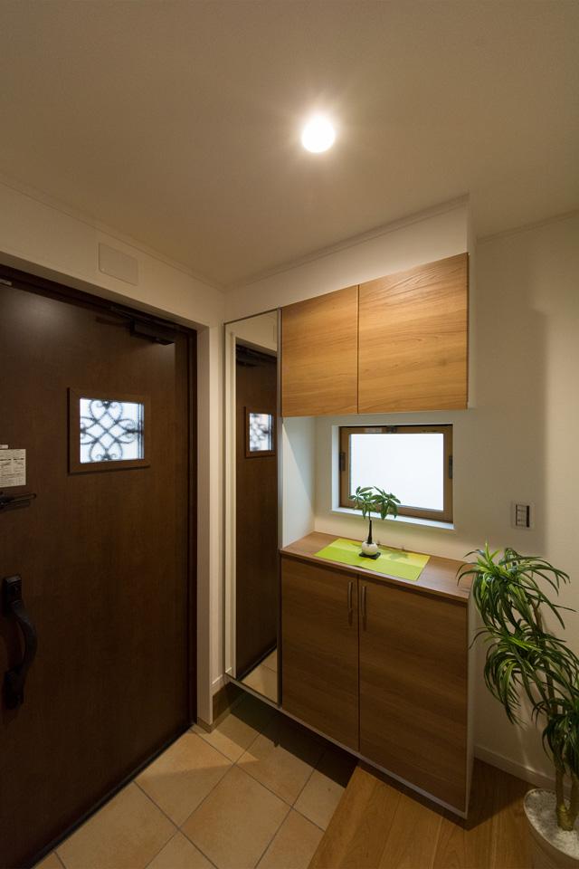 ラスティックウッドの玄関ドアとベージュのテラコッタ調タイルがナチュラルなエントランス空間を演出。