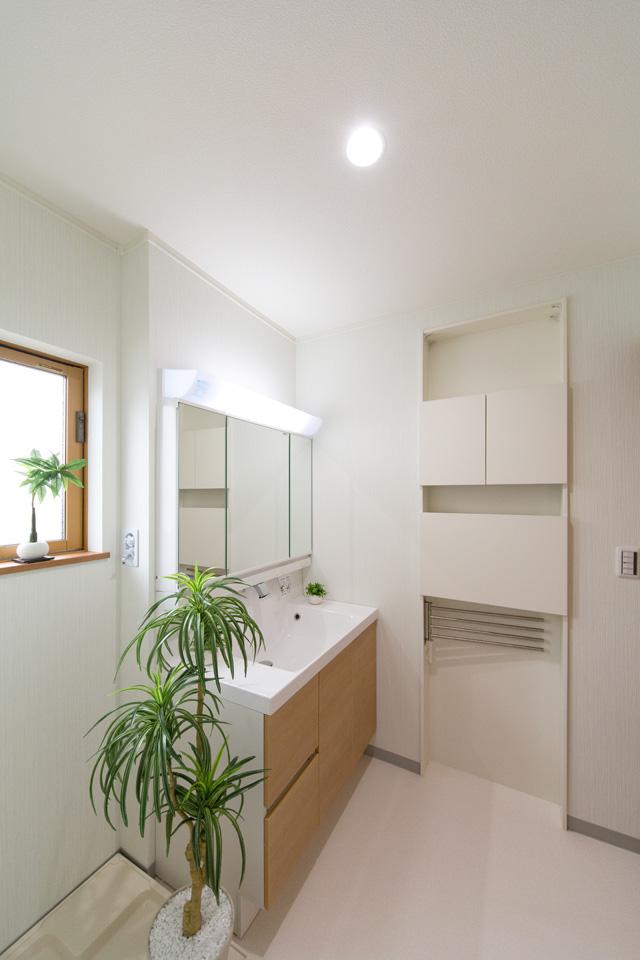 白を基調とした清潔感のある2階サニタリールーム。ブラウンの洗面化粧台がナチュラルな印象を与えます。