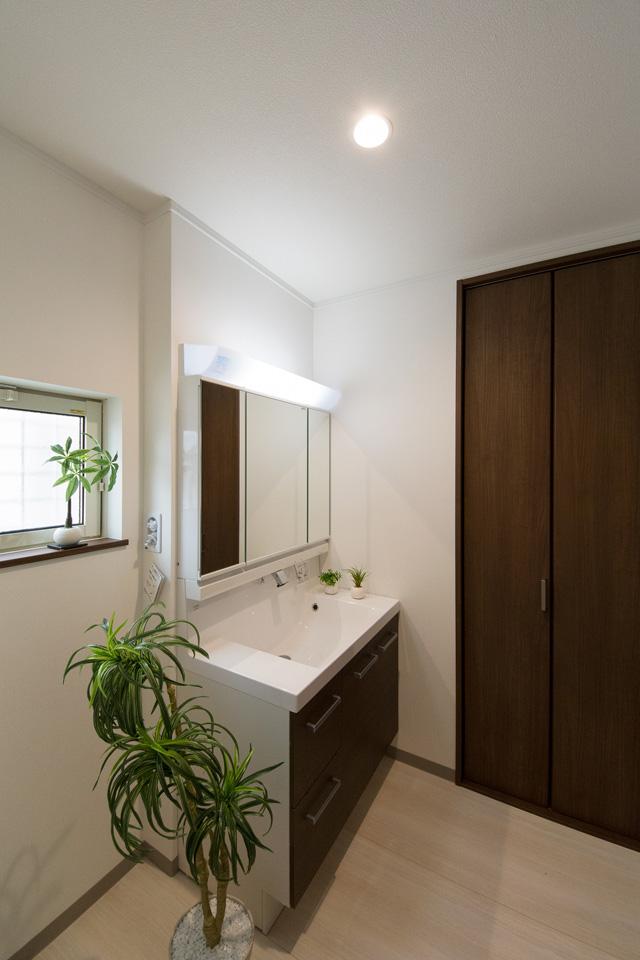 白を基調とした清潔感のあるサニタリールーム。ダークブラウンの洗面化粧台がナチュラルな雰囲気をプラス。