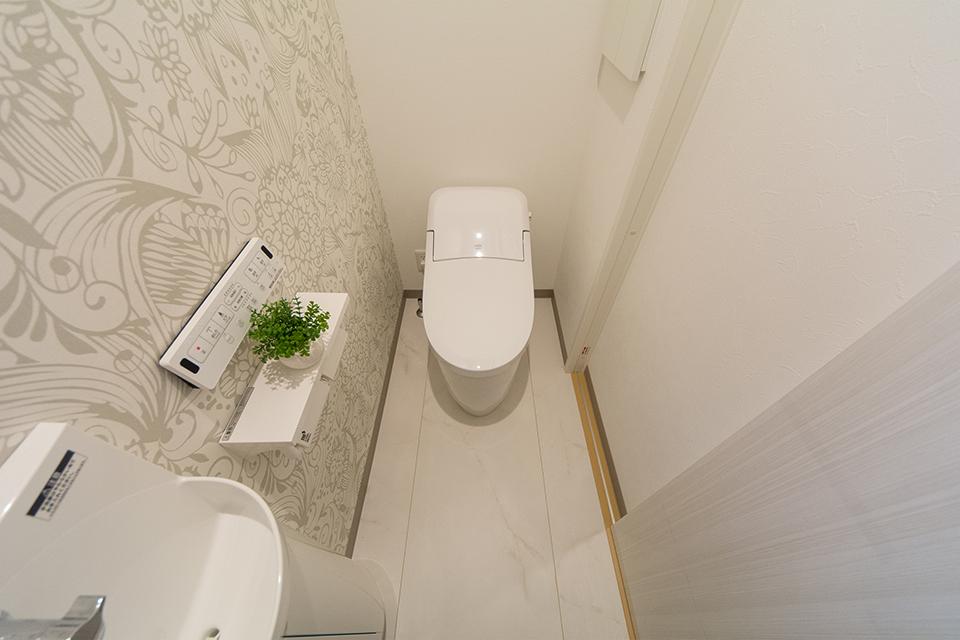 白を基調とした清潔感のある1階トイレ。アクセントクロスがエレガントな印象を与えます。