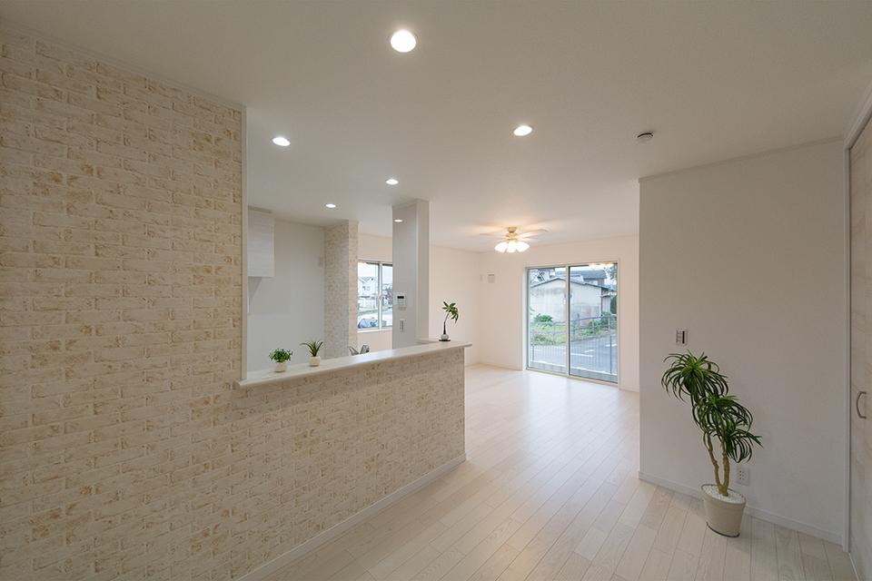 キッチンカウンター周りにあしらったブリック調のアクセントクロスがナチュラルな空間を演出。