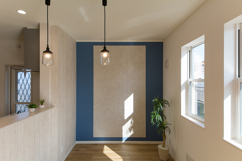 空気を美しく整えるインテリア壁材「エコカラット」とブルーのアクセントクロスをあしらった壁面が、リビング空間を爽やかに彩ります。