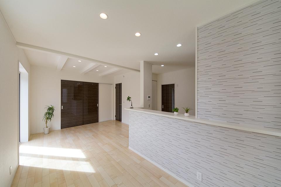 キッチンまわりにあしらったグレーのアクセントクロスが、ナチュラルな空間にモダンな印象をプラス。