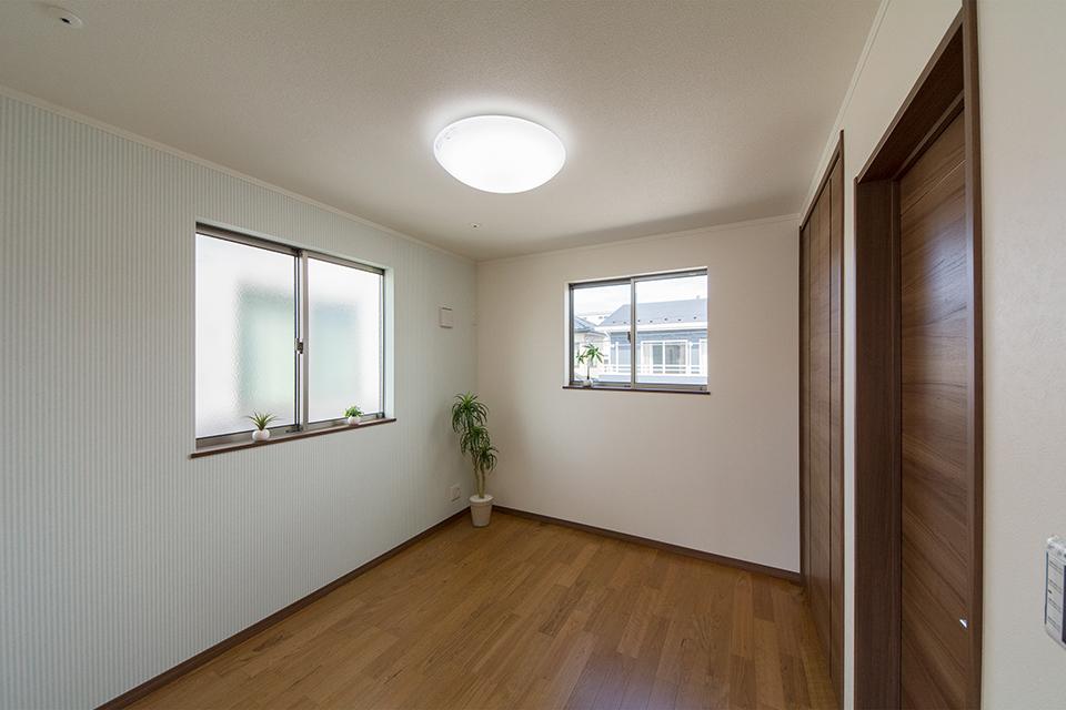ライトグリーンのストライプ柄アクセントクロスが印象的な2階洋室。