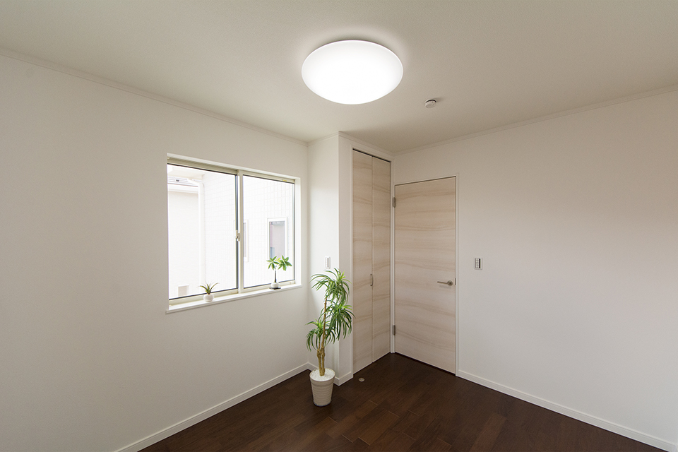 2階洋室。ウォルナットのフローリングがナチュラルな空間を演出。