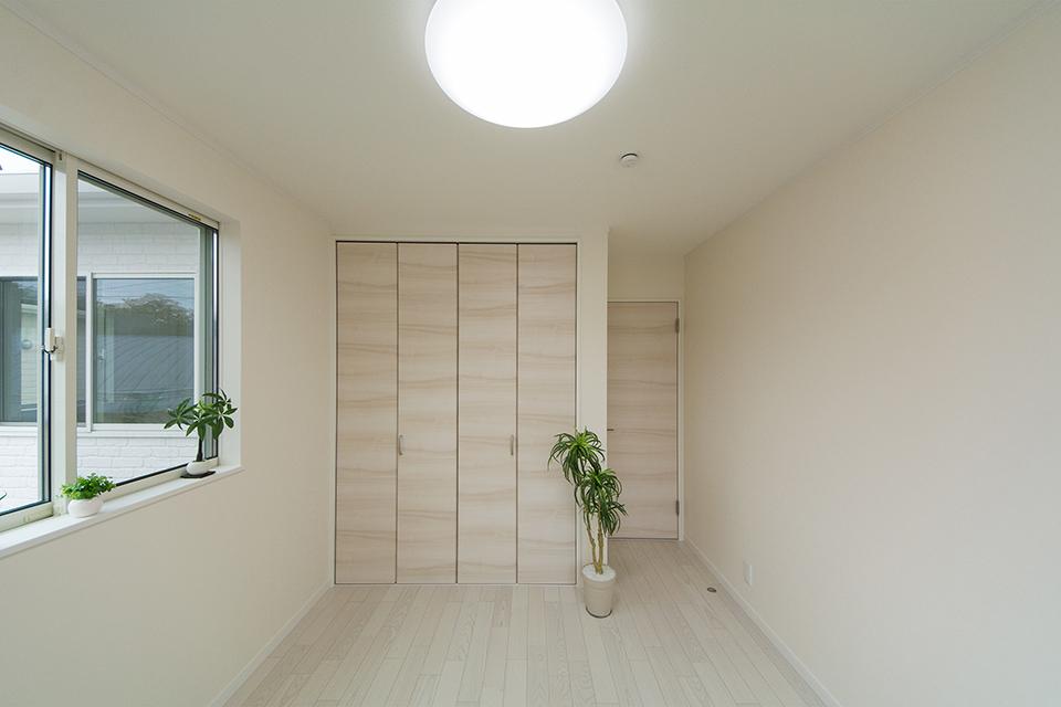 2階洋室。ホワイトアッシュのフローリングとイタリアンウォルナット調の建具が洗練された空間を演出。