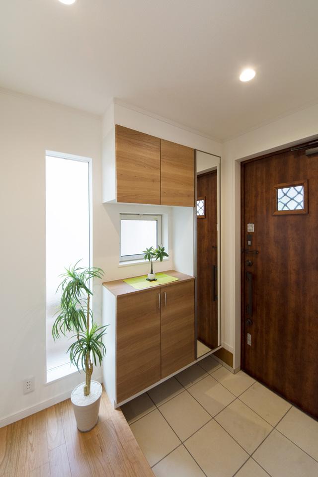 ナチュラルな雰囲気を演出するハンドダウンチェリーの玄関ドア。小窓部分とホールの縦窓から差し込む光が、明るく開放的ある空間を演出。