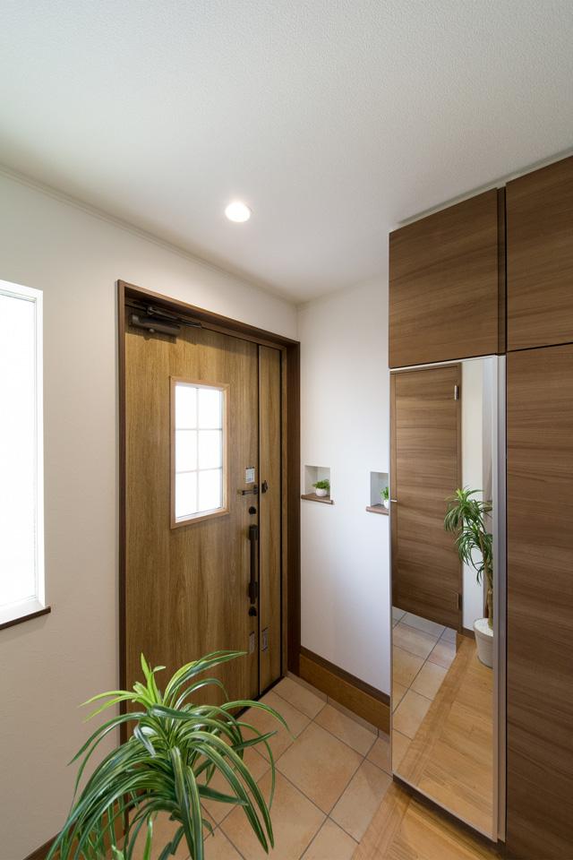 ナチュラルな雰囲気を演出するシュガーオークの玄関ドア。窓部分から差し込む光が、明るく開放的ある空間を演出。
