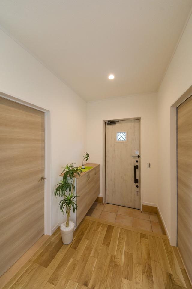 ナチュラルな雰囲気を演出するエクリュアイボリーの玄関ドア。小窓部分から差し込む光が、明るく開放的ある空間を演出。