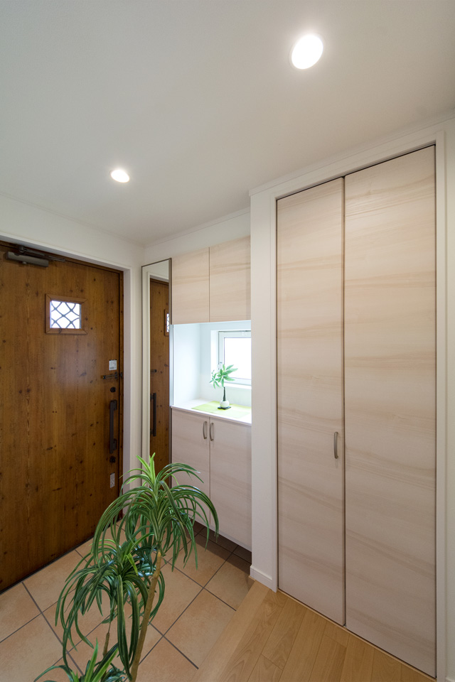ナチュラルな印象のアイリッシュパイン調玄関ドア。窓部分から差し込む光が、明るく開放的ある空間を演出。