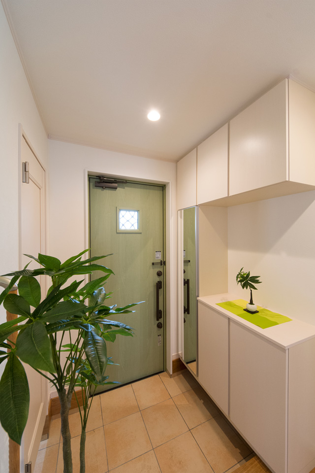 リーフグリーンの玄関ドアとベージュのテラコッタ調タイルがナチュラルな空間を演出。