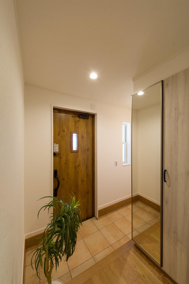 マキアートパインの玄関ドアとベージュのテラコッタ調タイルがナチュラルなエントランス空間を演出。