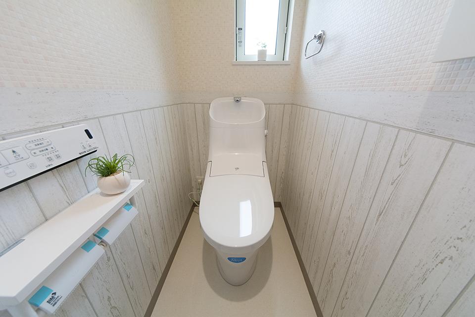 白を基調とした清潔感のある1階トイレ。木目調のアクセントクロスがナチュラルな雰囲気を演出。